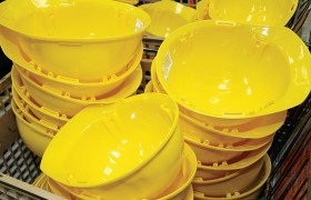Yellow helmet shells await assembly. The shells are made from high-density polyethylene.