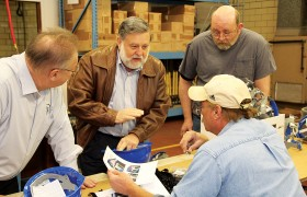 Jud Crosby (center), ERB's Technical Director, talks with employees about the correct assembly of the helmets.