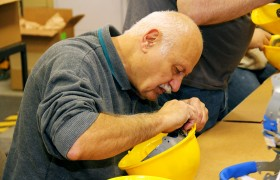 Bob Balach, a visually impaired employee, works to properly insert the suspension into the helmet shell.