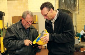 Jonathan Fister, CEO (left), and Allen Connely, Executive Vice President of Operations, examine a fully assembled helmet.