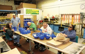 The helmet assembly line starts by inserting the suspension into the shell. Next, an information sheet and chin strap are placed in each helmet. The helmets are then wrapped and placed into boxes for shipping.